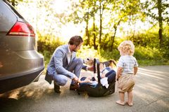 Young father with baby and toddler by the car. Young father with two children by the car. Baby girl in the car seeat. Little boy walking Stock Images