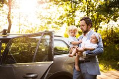 Young father with baby and toddler by the car. Man carrying baby girl and toddler boy Royalty Free Stock Images