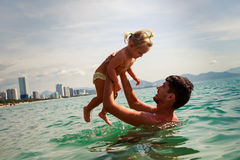 young father backside view holds little daughter above water Royalty Free Stock Images