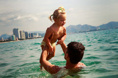 Young father backside view holds little daughter above water Stock Photo