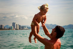 young father backside view holds little daughter above water Stock Image