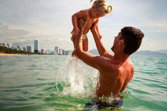 young father backside view holds little daughter above water Royalty Free Stock Image