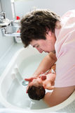 Young father bathing his newborn baby in the hospital Royalty Free Stock Images