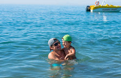 Young father in black sunglasses and smiling baby boy son in green baseball cap playing in the sea in the day time. Positive human Stock Images