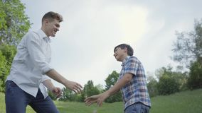 Young father and the boy high five and shaking hands outdoors. Father and a kid having fun in the park. Friendly family stock video footage