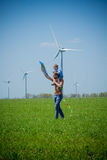 A young father carries a child on his shoulders and a kite near wind generators stock photo