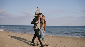 A young father carries his son in his shoulder, a young family walk by seashore, enjoy a joint weekend in nature. A. Woman in love looks at a man. Love, family stock video footage