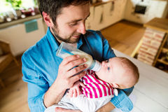 Young father carrying and feeding his newborn baby son Stock Photos