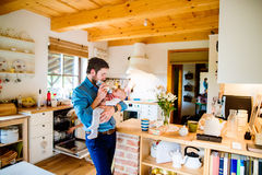 Young father carrying and feeding his newborn baby son Royalty Free Stock Photo