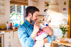 Young father carrying and feeding his newborn baby son Stock Photography