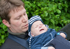 Young father carrying son in sling in park Royalty Free Stock Photos