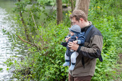 Young father carrying son in sling in park Royalty Free Stock Image