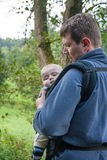 Young father carrying son in sling in summer forest Royalty Free Stock Photos