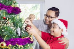 Young father with a child decorating Christmas tree. Young father with his son decorating a Christmas tree while having fun at home royalty free stock image