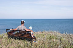 Young father with child sitting on the bench near the sea ocean. Royalty Free Stock Photography