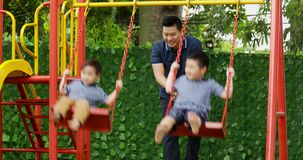Young father and children playing on swing