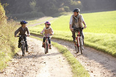 Young father with children ride bikes in park Royalty Free Stock Photos