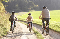 Young father with children ride bikes in park Stock Image