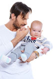 Young father cradling his baby on his arm. Young loving father cradling his smiling happy baby on his arm, upper body studio portrait on white Stock Image