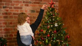 Young Father with Cute Daughter on His Hands Are Decorating the Christmas Tree. Happy New Year. Father`s Day. HD, Together, Family, Good Mood stock video
