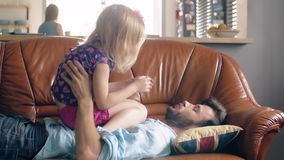 A young father and cute happy little daughter are playing on the sofa in the living room. 4k stock video footage