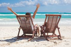 Young father with daughter in beach chairs raised Royalty Free Stock Images