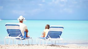 Father and daughter on tropical beach sitting on chaise-longue enjoying the view of Atlantic Ocean stock video footage