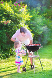 Young father and daughter grilling in the garden Royalty Free Stock Image