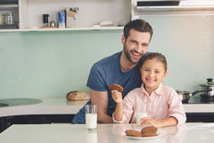 Young father and daughter having a snack meal. Young father and his daughter having snack milk and cookies in kitchen Royalty Free Stock Image