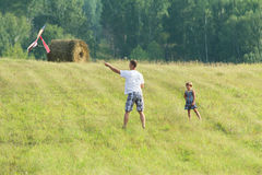 The young father with the daughter on meadow let in kite flight Royalty Free Stock Photos