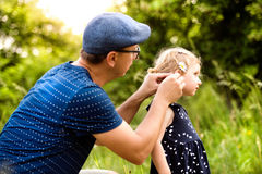 Young father with daughter in nature doing her hairstyle. Royalty Free Stock Images