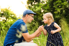 Young father with daughter in nature doing her hairstyle. Stock Photo
