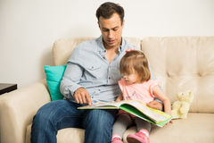 Young father and daughter reading Stock Photos