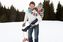 Young Father And Daughter In Snow With Sled Royalty Free Stock Images