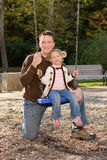 Young father with daughter on swing. Young father kneeling by little daughter on swing at Cascade Park, Bloomington, IN Royalty Free Stock Image