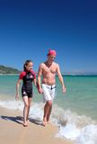 Young father and daughter walking along sunny beach royalty free stock image