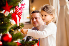 Young father with daugter decorating Christmas tree together. Young father with his little daughter at home decorating Christmas tree together royalty free stock images