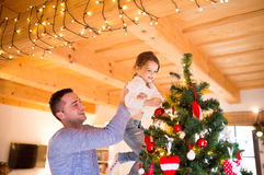 Young father with daugter decorating Christmas tree together. Young father holding his little daughter in his arms at home decorating Christmas tree together Stock Photography