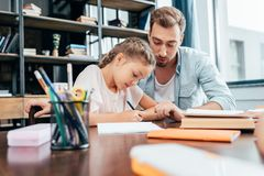 Young father doing homework. With little daughter stock photo
