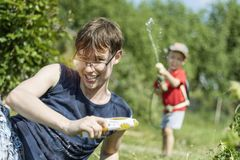 Young father or elder brother and a little boy - a son - play water guns outdoors in the summer among green grass. A blurry. Toddler suddenly shoots in the back royalty free stock photos