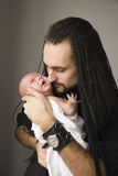 The young father embraces the baby. The young father with the baby on hands on a gray background Royalty Free Stock Photos