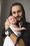 The young father embraces the baby. The young father with the baby on hands on a gray background Stock Photo