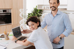 Young father explaining geography to his son. Grateful student. Upbeat bearded men posing near the laptop and being about to explain his son some geography while Royalty Free Stock Images