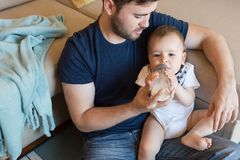 Father feeding baby. Young father feeding his baby with nursing bottle Royalty Free Stock Photo