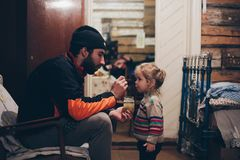 Young father feeding his little girl at home, fatherhood. stock photography