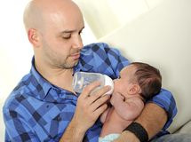 Young father feeding newborn baby with milk bottle on couch at home stock photography