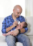 Young Father Feeding Newborn Baby With Milk Bottle On Couch At Home Royalty Free Stock Photos