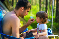 Young father feeds his daughter seeds on vacation in woods. Stock Photo