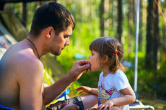 Young father feeds his daughter seeds on vacation in  woods. Royalty Free Stock Images