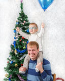 Young father with funny boy on his shoulders near New Year fir. Tree Stock Photo